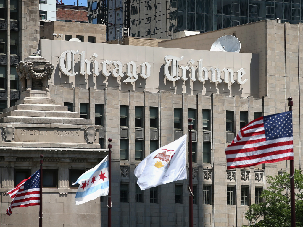 Flags fly along the Michigan Avenue bridge near the Tribune Tower, home of the <em>Chicago Tribune </em>in Chicago, in 2013. <em>Tribune </em>journalists have given corporate owner Tronc a day to recognize the union voluntarily.