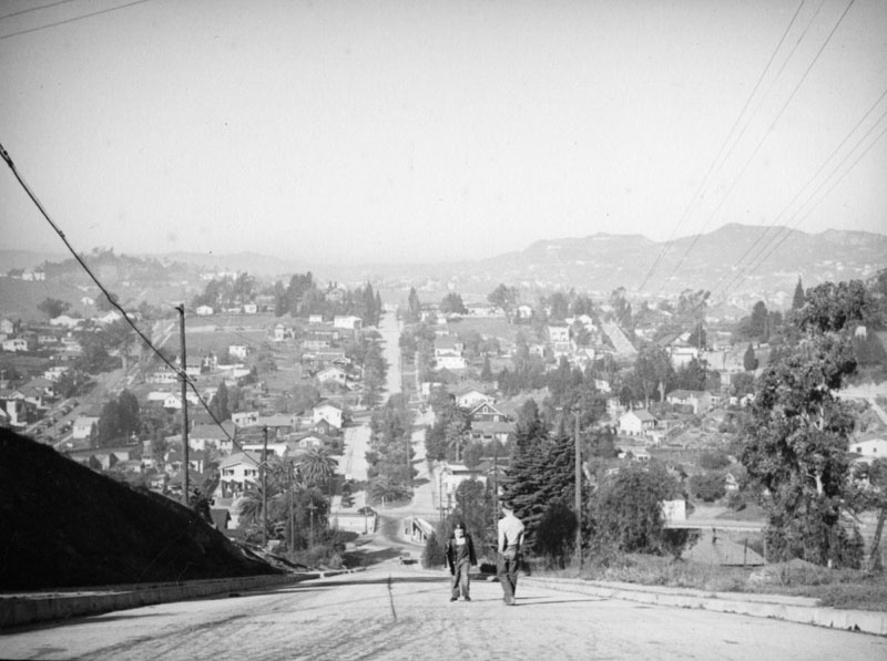 Looking northwest towards Silver Lake, Los Feliz, and Griffith Park from Baxter Street in Echo Park. Two boys are seen walking up the very steep street.
