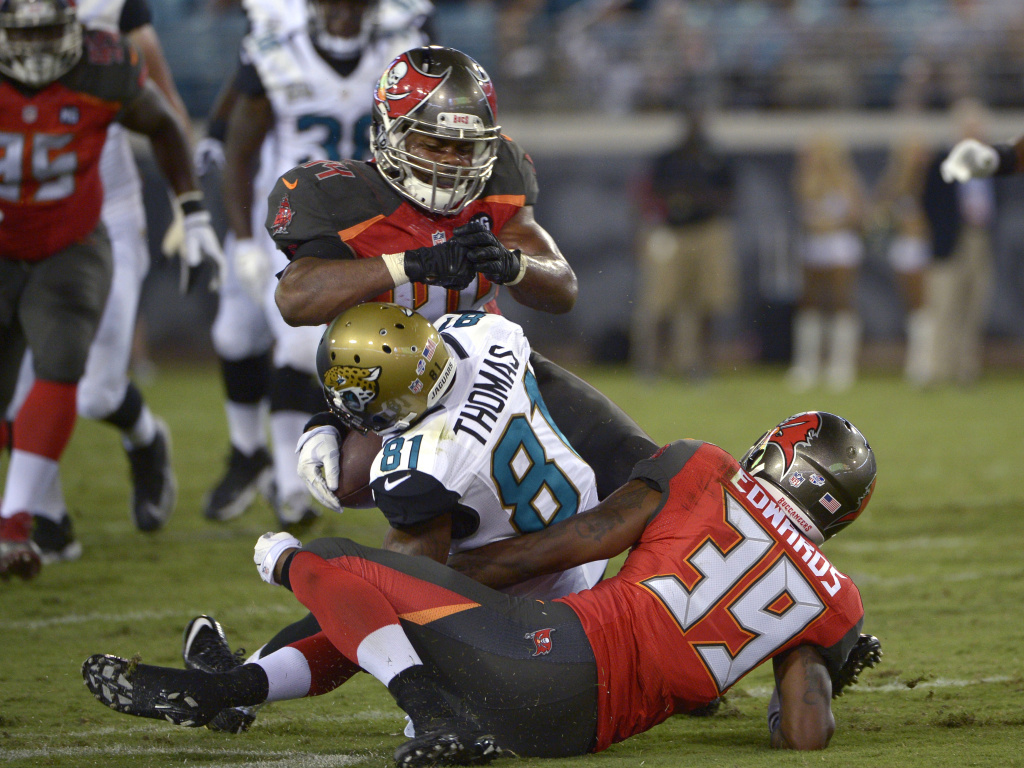 Jacksonville Jaguars wide receiver Lamaar Thomas, center, is hit in the head by Tampa Bay Buccaneers linebacker Brandon Magee, top, as cornerback Kip Edwards helps make the tackle a 2014 preseason game. Magee was penalized for the hit.