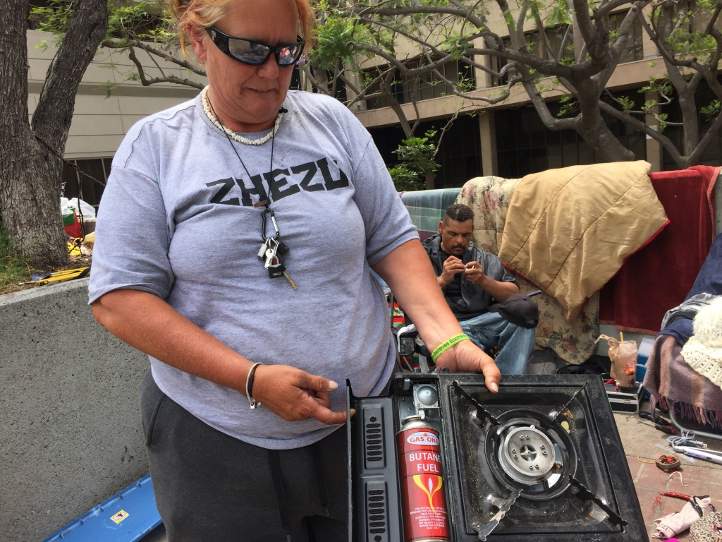 Kim Sandoval, 46, uses a small burner to boil water and cook small meals, mostly coffee and Ramen Noodle soup. Orange County homeless people and activists want the county to enroll in a federal program that allows homeless people on foods stamps to use them at restaurants.