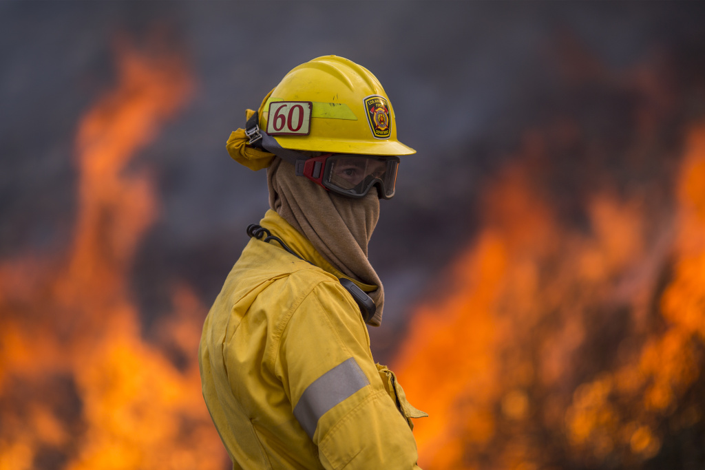 Flames rise behind a firefighter at the La Tune Fire on September 2, 2017 near Burbank.