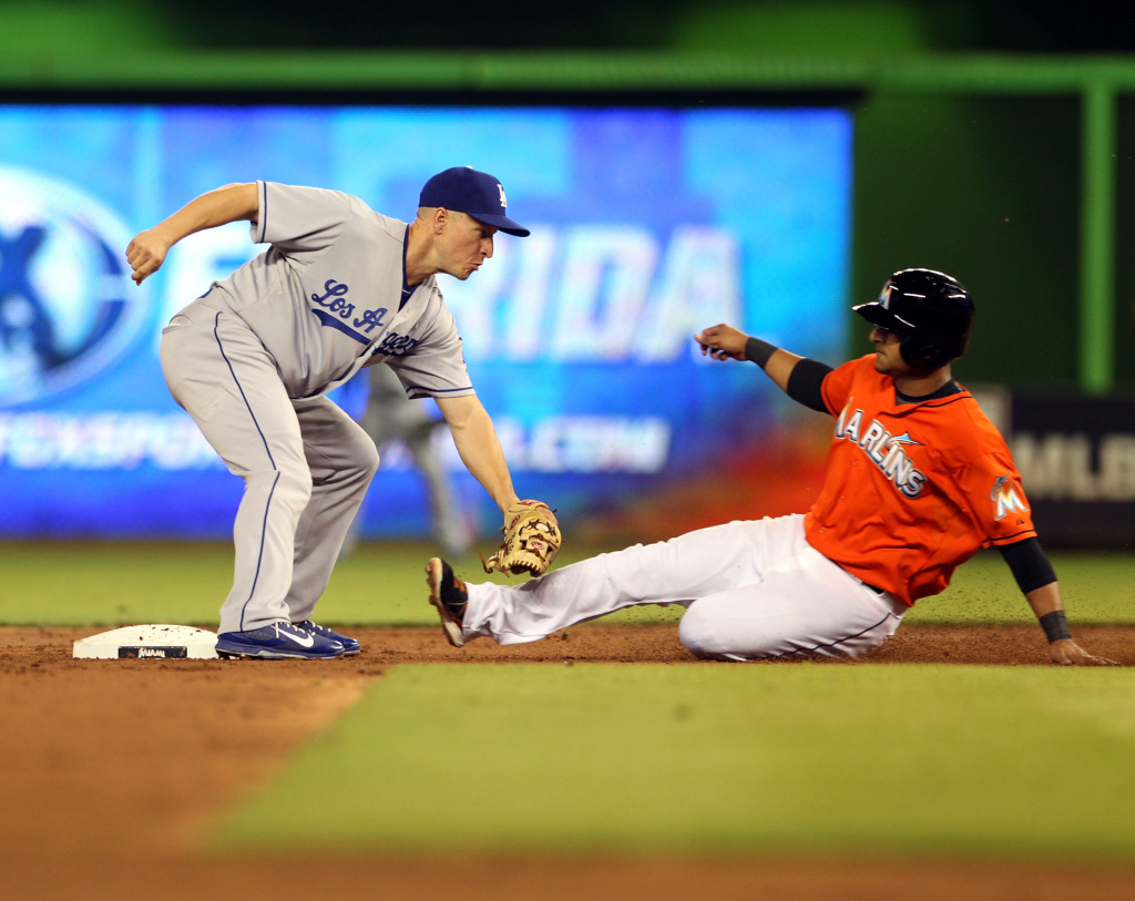Donovan Solano #17 of the Miami Marlins slides into a double play by second baseman Mark Ellis #14 of the Los Angeles Dodgers at Marlins Park on August 19, 2013 in Miami, Florida.