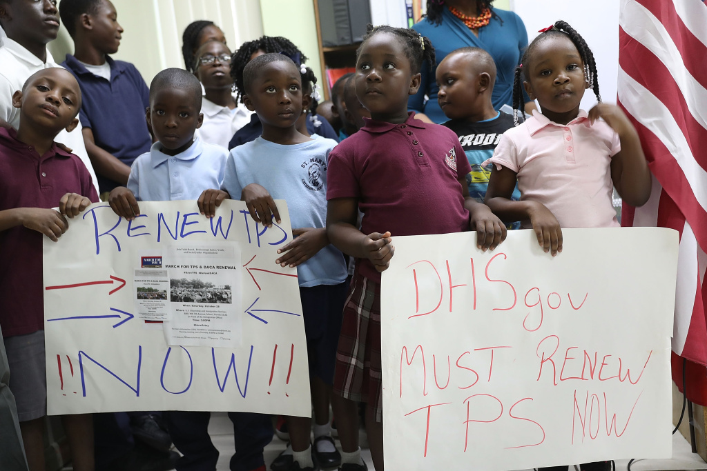 Children hold posters asking the Federal government to renew  Temporary Protected Status during a press conference about TPS for people from Haiti, Honduras, Nicaragua and El Salvador at the office of the Haitian Women of Miami in the Little Haiti neighborhood on Nov. 6, 2017 in Miami, Florida.