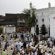 People gather outside All Saints Church in Peshawar, Pakistan, in 2013 after a suicide bombing attack killed scores of people earlier in the day, officials said. This Sunday another suicide bombing hit a popular park in Lahore.