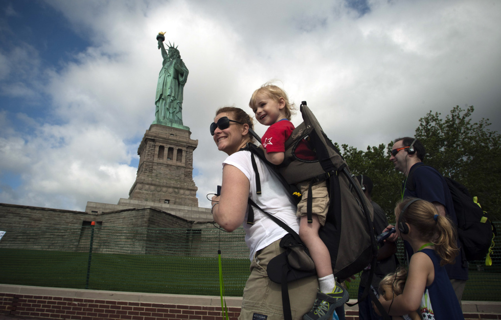 A family walks by the Statue of Liberty on July 4, 2013 on the Liberty Island in New York City.