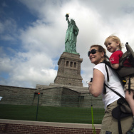 A family walks by the Statue of Liberty on the first day it is open to the public after Hurricane Sandy on July 4, 2013 on the Liberty Island in New York City.