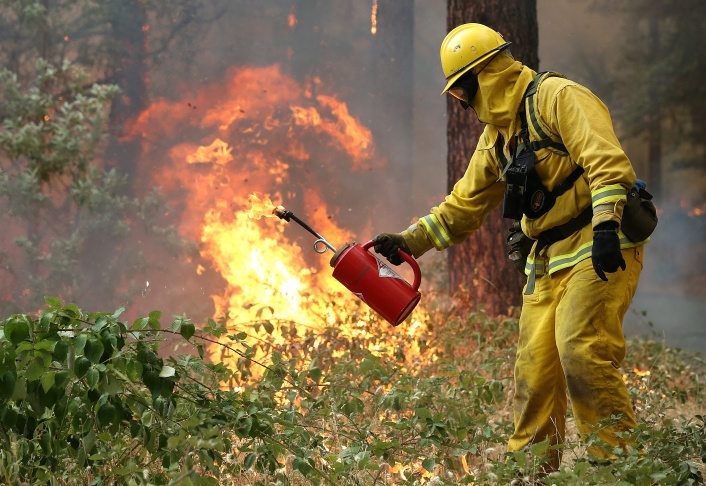 GROVELAND, CA - AUGUST 21:  Firefighters from Ebbetts Pass Fire District monitor a back fire as they  battle the Rim Fire on August 21, 2013 in Groveland, California. The Rim Fire continues to burn out of control and threatens 2,500 homes outside of Yosemite National Park. Over 400 firefighters are battling the blaze that is only 5 percent contained.  (Photo by Justin Sullivan/Getty Images)