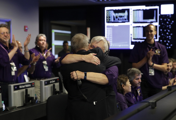 Project manager Earl Maize, center, left, and flight director Julie Webster hug in mission control at NASA's Jet Propulsion Laboratory, Friday, Sept. 15, 2017, in Pasadena, Calif., after confirmation of Cassini's demise. Cassini disintegrated in the skies above Saturn early Friday, following a remarkable journey of 20 years. (AP Photo/Jae C. Hong, Pool)