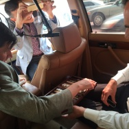 "Off-Ramp host John Rabe and Mayor Eric Garcetti playing backgammon in John's car. Julian ""The First Lady of Off-Ramp"" Bermudez in the passenger seat with camera."