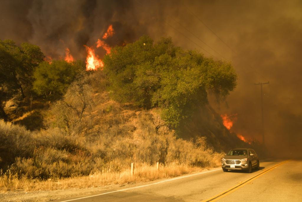 The Sand Fire burns intensely off Placerita Canyon Rd Sunday afternoon as a media vehicle races away from flames.    The Sand Fire burns in the Angeles National Forest Sunday July 24th, 2016 under a Red Flag Warning high high winds. The fire had burned 22,000 acres by Sunday morning and was 10% contained as firefighters battled low humidity, shifting wind, and high temperatures. An unknown number of structures were lost.