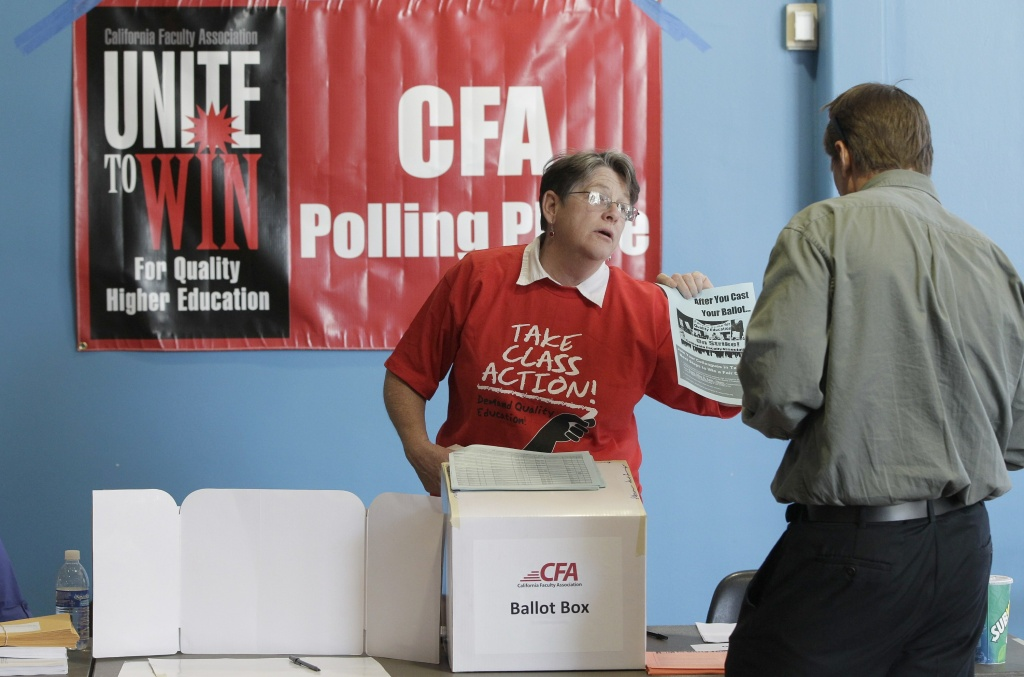 In this file photo, California Faculty Association (CFA) member, professor Deborah Haam, left, helps Long Beach California State University employees vote Monday, April 16, 2012. On Tuesday, November 11, 2014, the CFA said its members had voted to ratify a three-year contract that includes a pay raise.