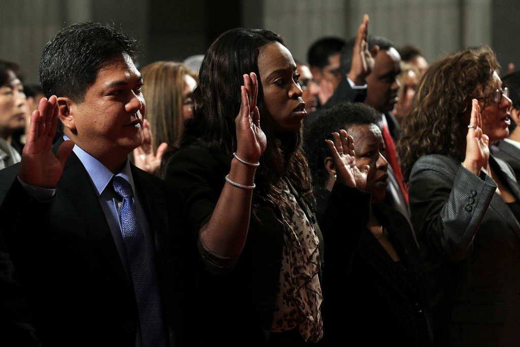 New citizens are sworn in during a naturalization ceremony at Department of Interior September 23, 2011 in Washington, DC. According to one recent study, in 2011, only 61 percent of eligible legal permanent residents became U.S. citizens.