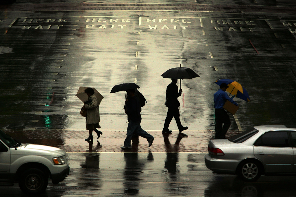 File: People walk in the rain downtown as a late-season Pacific storm brings rain and snow to Southern California April 20, 2007 in Los Angeles.