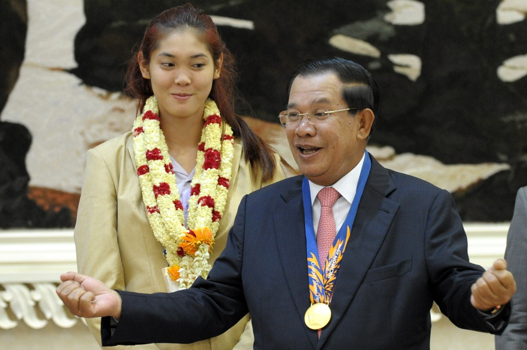 File: Cambodian Prime Minister Hun Sen gestures as Sorn Seavmey (behind), Gold medal winner in the woman's 73kg Taekwondo at the 17th Asian Games in Incheon, South Korea, looks on during a victory ceremony at the Peace Palace in Phnom Penh, on Oct. 5, 2014.