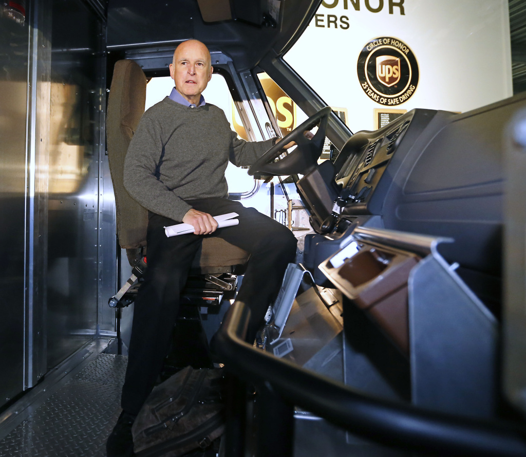 Gov. Jerry Brown sits in the driver's seat of a electric-powered UPS delivery truck at the UPS distribution center in West Sacramento, Calif., in February.  Brown was one of eight governors scheduled to gather in Sacramento on Thursday, Oct. 24, 2013, to sign a memorandum of understanding that would get 3.3 million zero-emission vehicles on roadways by 2025.