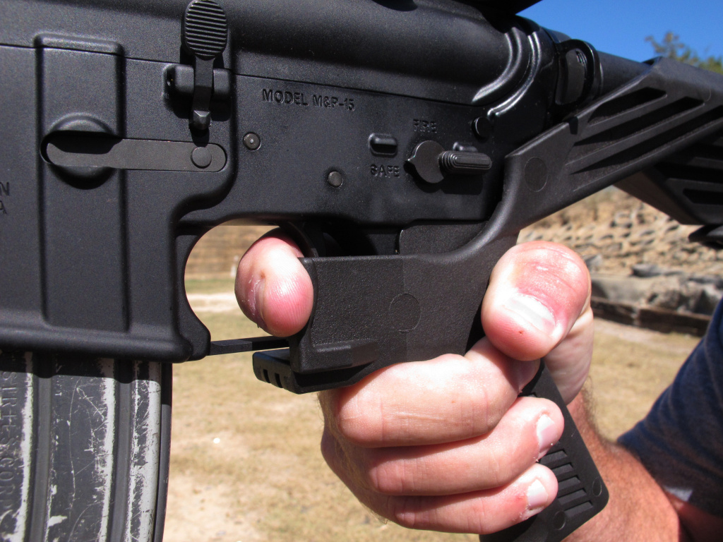Shooting instructor Frankie McRae illustrates the grip on an AR-15 rifle fitted with a