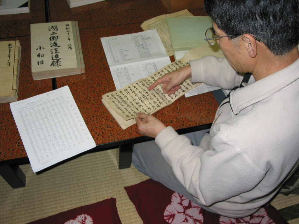 The Priest Mr. Kiyoshi Miyasaka pointing out some of the records on lake ice and the omiwatari. His data sheet summarizing the records are on the table. Taken Nov. 3, 2005.