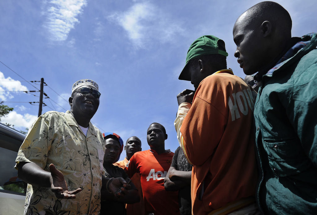 President Barack Obama's Kenyan half brother, Malik Obama (L) talks with some of his supporters on January 16.