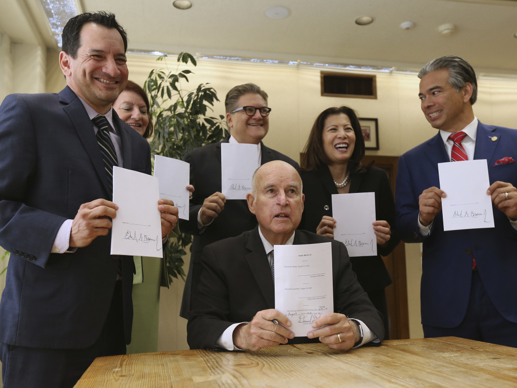 Gov. Jerry Brown holds a copy of a bill to end bail he signed Tuesday, Aug. 28, in Sacramento, Calif. The bill, co-authored by state Sen. Bob Hertzberg, D-Van Nuys, third from right, and Assemblyman Rob Bonta, D-Alameda, right, makes California the first state to eliminate bail for suspects awaiting trial. It goes into effect in October 2019.
