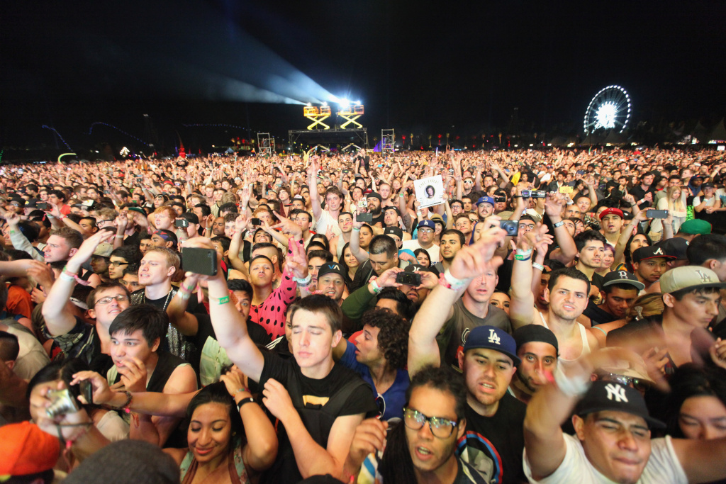Fans watch rappers Dr. Dre (L) and Snoop Dogg perform onstage during day 3 of the 2012 Coachella Valley Music & Arts Festival at the Empire Polo Field on April 15, 2012 in Indio, California.