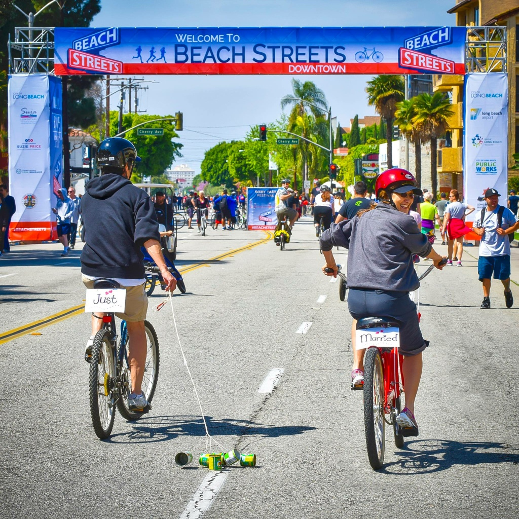 Newly married bicyclists pedal through Long Beach during a Beach Streets event.