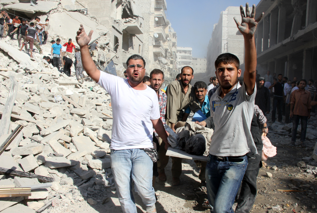 Syrian men evacuate a victim following an air strike by regime forces in the northern city of Aleppo on August 26, 2013. Syria's opposition accused pro-regime forces of opening fire at UN weapons inspectors on their way to a suspected chemical weapons site outside Damascus in a bid to hinder their investigation.