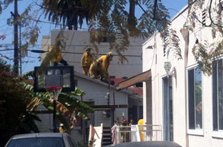 Firefighters removing a huge object that flew onto the roof of a home near a synagogue in Santa Monica on April 7, 2011.