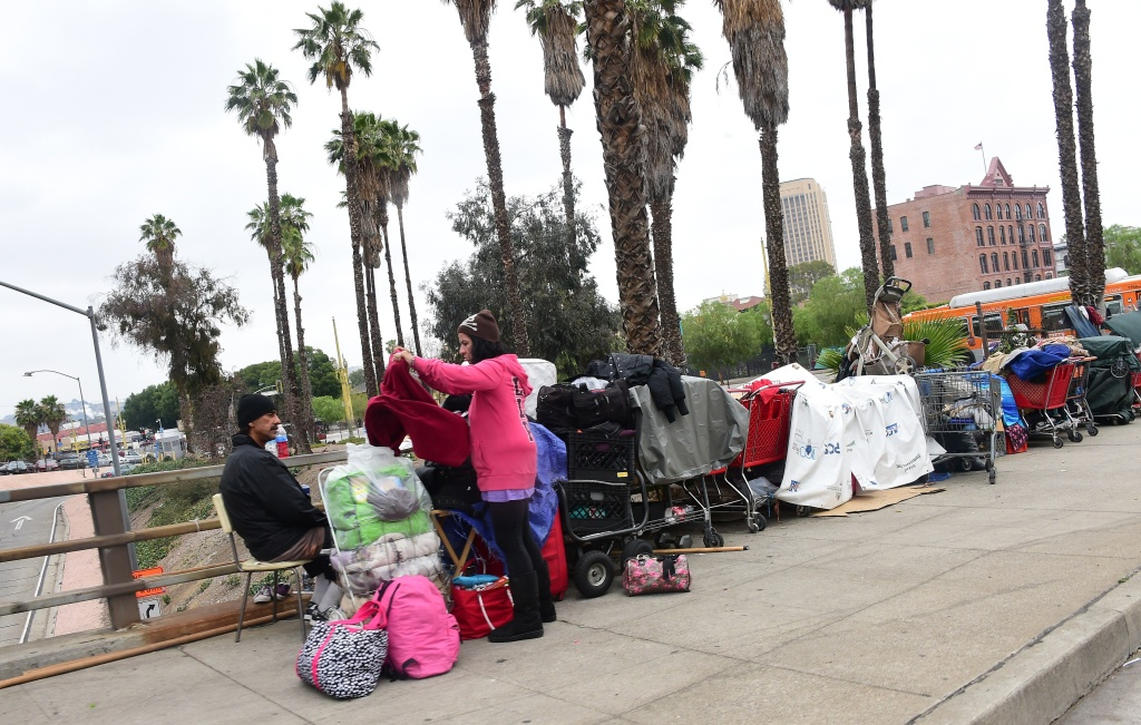 A woman folds clothes at a homeless encampment above a downtown Los Angeles freeway on May 12, 2015.