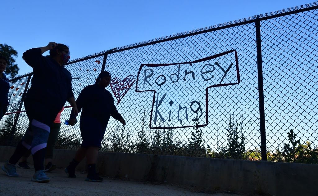 People walk past the name Rodney King seen on a chain-link fence surrounding Silver Lake Reservoir in Los Angeles, on June 9, 2020.
