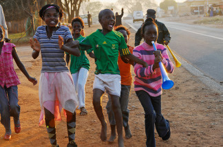 Children of Mamelodi Township celebrate during halftime after South Africa scored two goals in the first half against France during the 2010 World Cup match on June 22, 2010 east of Pretoria, South Africa.