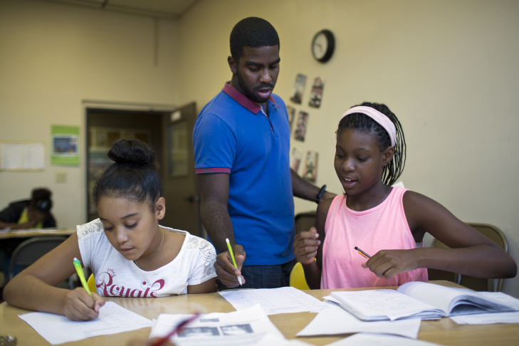 Teaching assistant Jonathan Curtiss checks the work of Alyse Wilson, 11, left, and Kayla White, 12, during the fourth week of a pre-algebra class at the West Angeles Church Youth Center on Thursday afternoon, July 30, 2015.