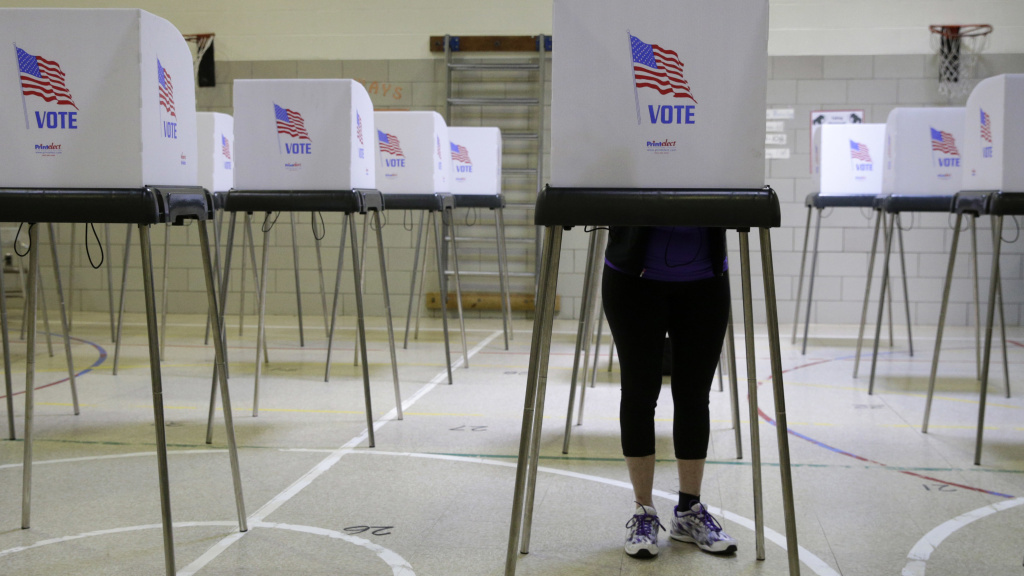 A woman casts her vote at a polling place inside Winfield Elementary School's gym in Windsor Mill, Md.