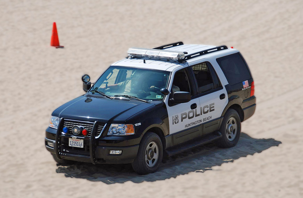 A Huntington Beach Police SUV drives on the beach.