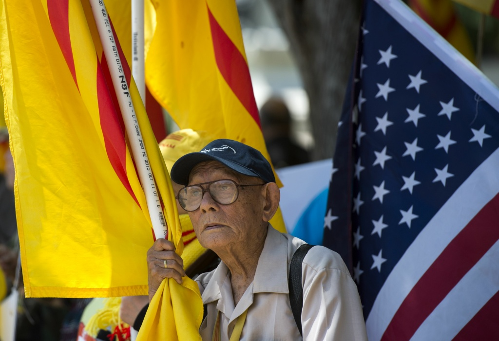 A protester holds a Vietnamese flag red flag with gold star designed in 1940 and used during an uprising against French rule in southern Vietnam, during a rally against the visit of Vietnamese Prime Minister Nguyen Xuan Phuc to the White House in Washington, DC on May 31, 2017.