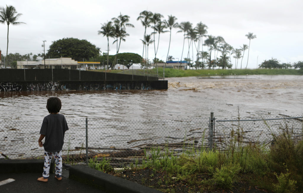 A boy views floodwaters from Hurricane Lane rainfall on the Big Island on August 23, 2018.