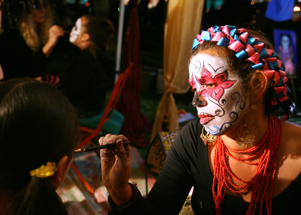 A woman paints a girl's face for Día de los Muertos.