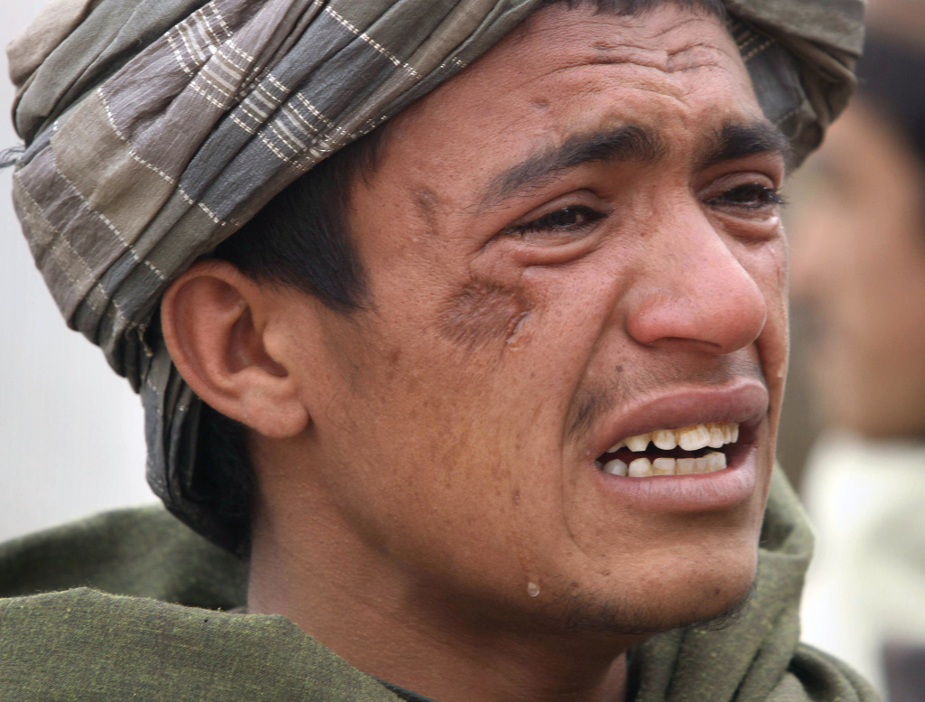 An Afghan youth mourns for relatives, who were allegedly killed by a U.S. service member in Panjwai, Kandahar province south of Kabul, Afghanistan. A U.S. service member walked out of a base in southern Afghanistan before dawn Sunday and started shooting Afghan civilians, according to villagers and Afghan and NATO officials.