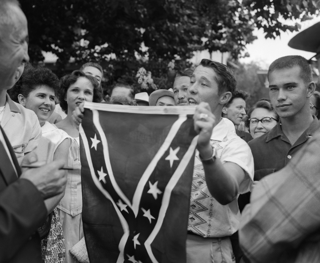 Paul Davis Taylor displays a Confederate flag in front of Little Rock Central High School on Sept. 3, 1957. Taylor was among some 500 people who gathered across the street from the school, which had been scheduled to integrate.