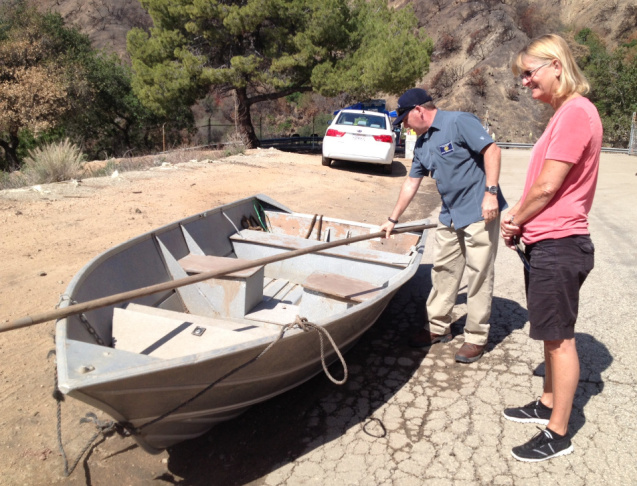 Area engineer Steve Sheridan with the Los Angeles County Public Works Department shows Glendora, Calif. resident Carol Coppel an aluminum boat that county workers sometimes use to manually clear vegetation from a drainage tower in the storm debris basins above Glendora. The tower allows water to drain, while mud that would otherwise flow downhill and potentially cause property damage collects in the basins.