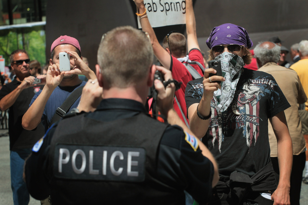 Using cameras a police officer squares off with protestors during a demonstration organized by National Nurses United in Daley Plaza where they were calling for a