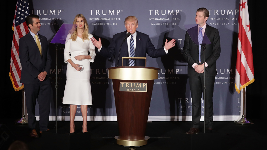 Donald Trump with his eldest children at the grand opening of the Trump International Hotel in Washington, D.C. Trump says he'll turn over control of his businesses to sons Eric and Donald, Jr.