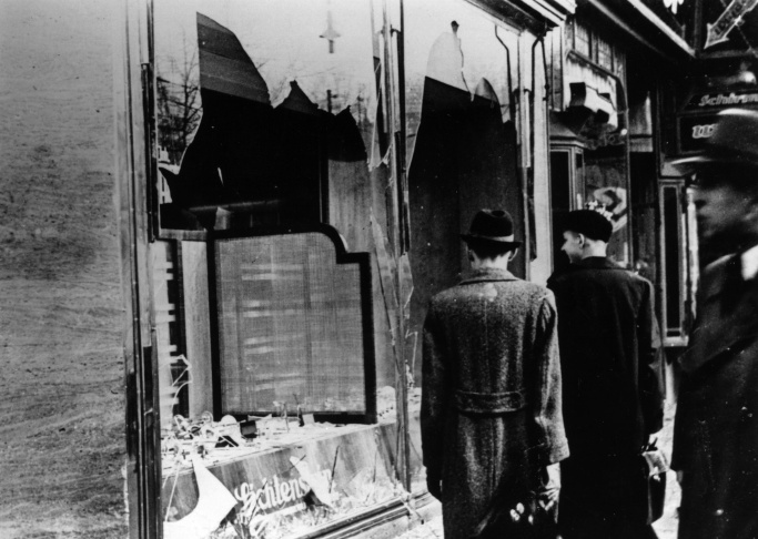 10th November 1938: Three onlookers at a smashed Jewish shop window in Berlin following riots of the night of 9th November.