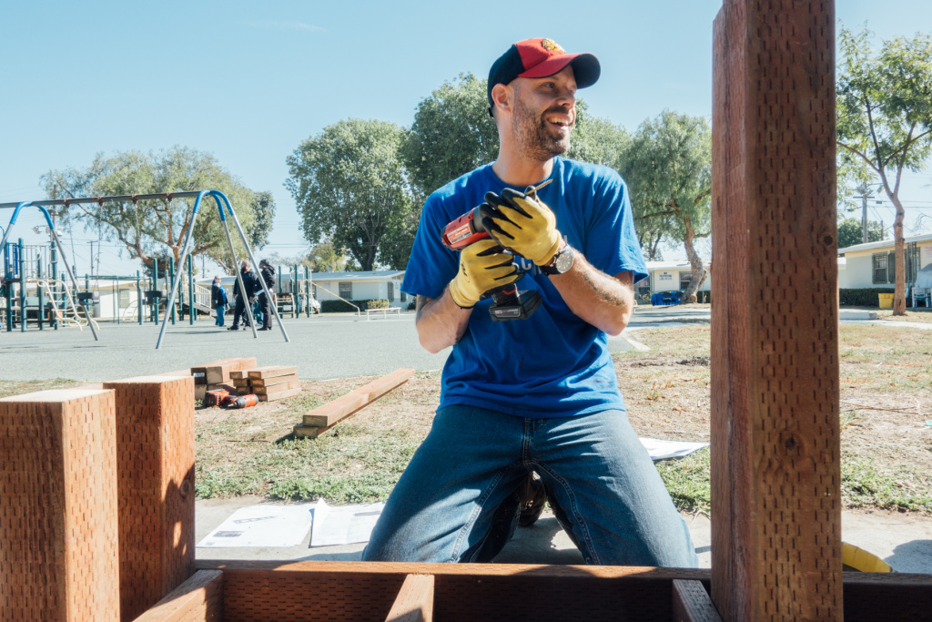 The Mission Continues volunteer Tony Worley wields a drill during a playground revitalization project at Gonzaque Village in Watts.