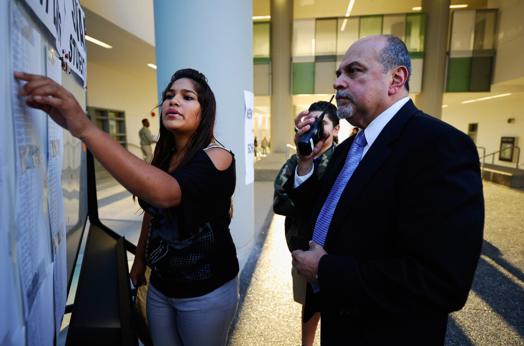 Chuck Flores one of six principals of the newly opened Robert F. Kennedy Community Schools complex helps Kerin Gonzalrz, 15, find her classroom.