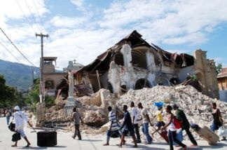 People walk by the collapsed Sacre Coeur Church in Port-au-Prince, on January 14, 2010, following the devastating earthquake that rocked Haiti on January 12.