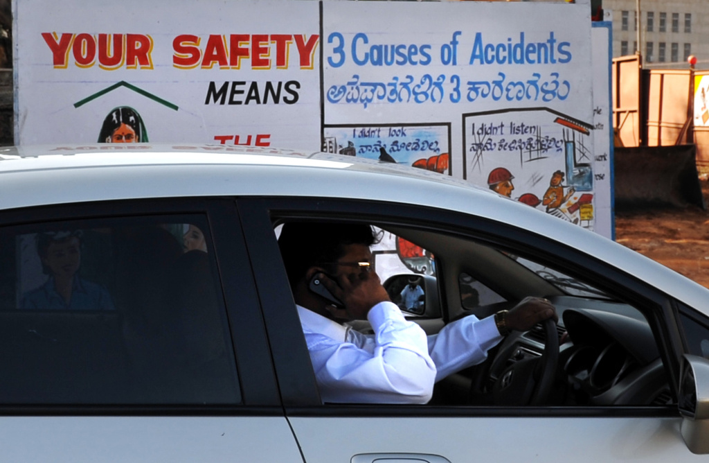 An Indian man talks on his mobile phone as he drives past a traffic awareness poster on the side of a busy road in Bangalore on January 27, 2011.AFP PHOTO/Dibyangshu SARKAR (Photo credit should read DIBYANGSHU SARKAR/AFP/Getty Images)
