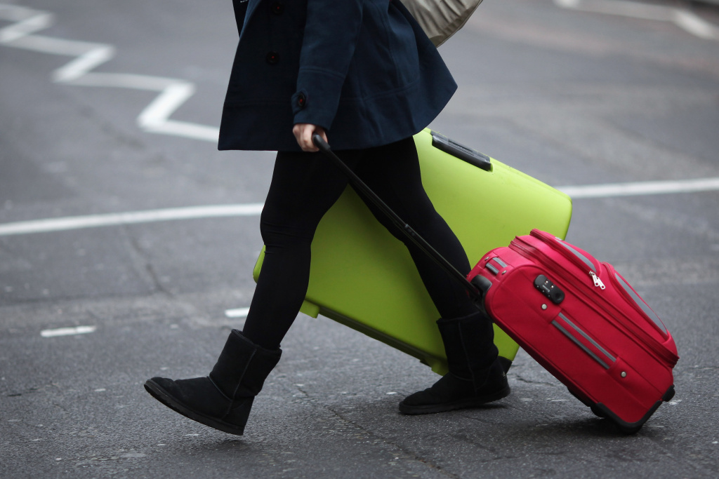 LONDON, ENGLAND - DECEMBER 23:  A woman drags her suitcases towards Victoria Coach Station on December 23, 2011 in London, England.