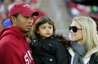 Honorary Stanford Cardinal captain Tiger Woods holds his daughter, Sam, and speaks to his wife, Elin Nordegren, on the sidelines before the Cardinal game against the California Bears at Stanford Stadium on November 21, 2009 in Palo Alto.