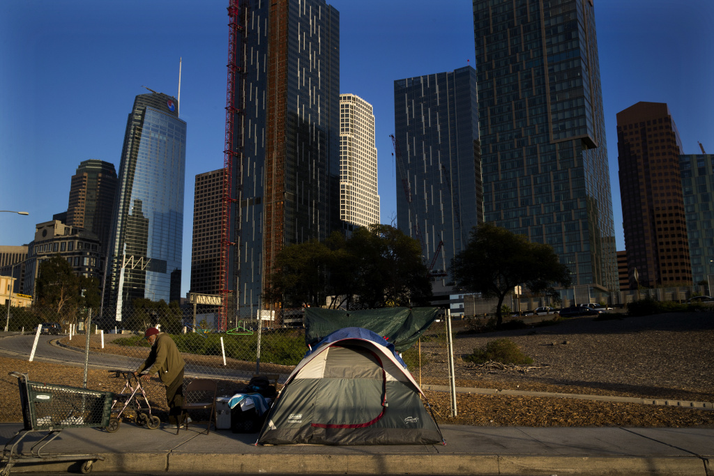 A homeless man, who declined to give his name, is dwarfed by skyscrapers Monday, Dec. 4, 2017, in Los Angeles.