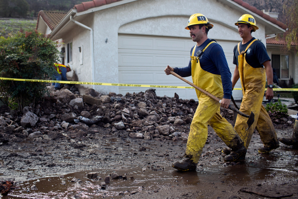 Ventura County Fire works to dig mud off streets after an overnight storm caused mudslides in Camarillo Springs on Friday afternoon, Dec. 12, 2014.